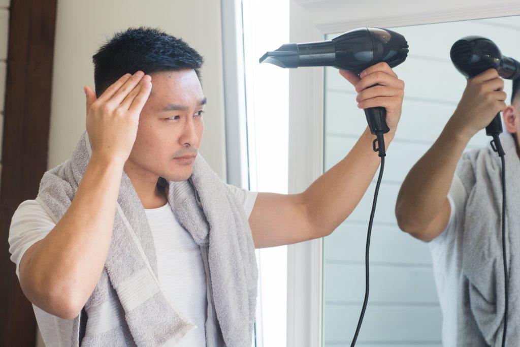 ドライヤーで髪を乾かす男性