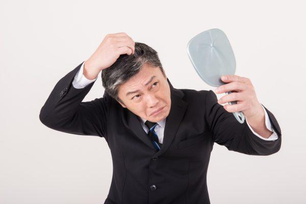 鏡を見ながら髪を気にする男性
