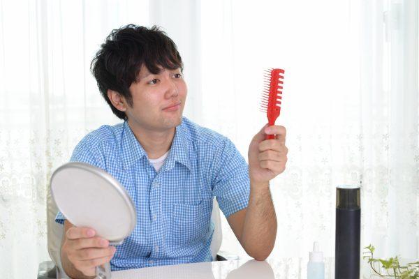 手鏡とヘアブラシを持つ男性