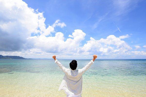海に向かって両手を上げる男性