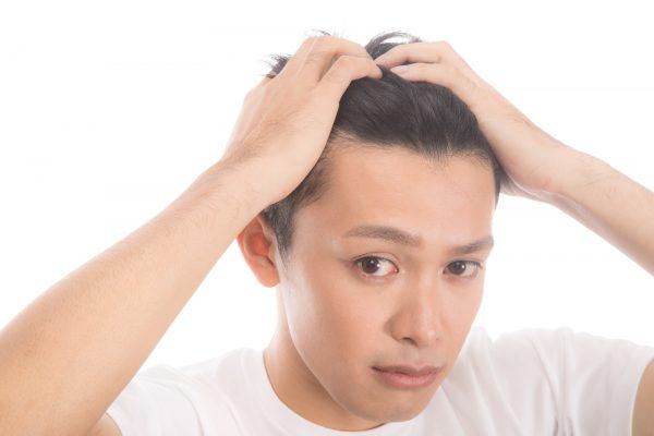 両手で髪をかき上げる男性