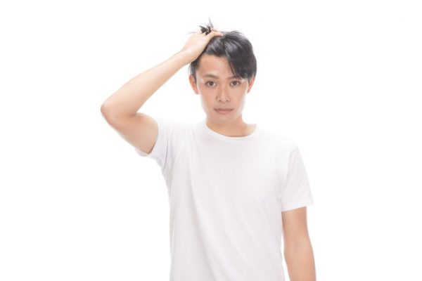 髪をかきあげる男性