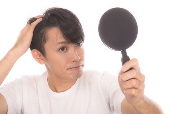 鏡で髪を見る男性