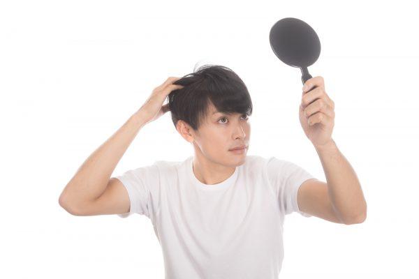 手鏡を見ながら髪を気にする男性