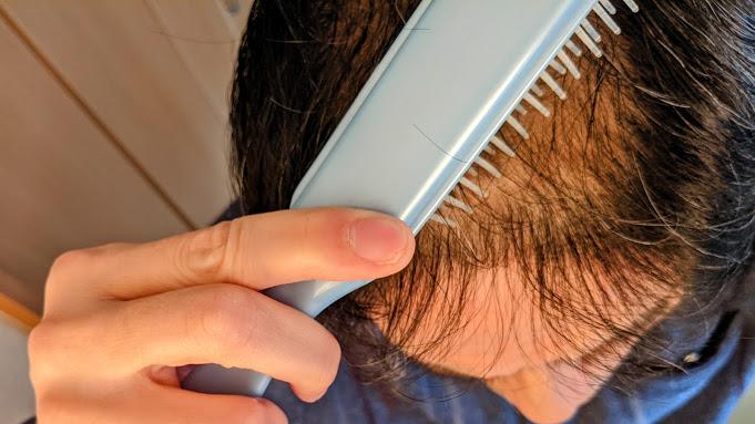 髪の薄い頭を櫛で梳く男性