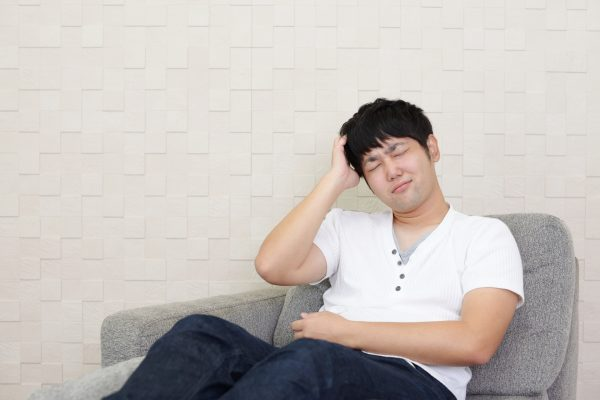 ソファーに座って考え事をする男性