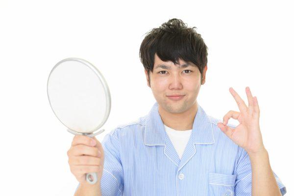手鏡を持って微笑む男性