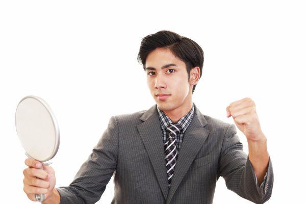 手鏡を持ってこちらを見る男性