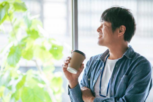 飲み物を持つ笑顔の男性