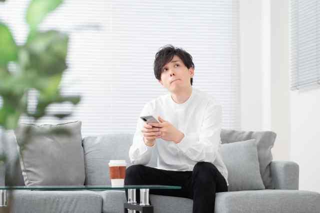 携帯電話を持って考え事をする男性