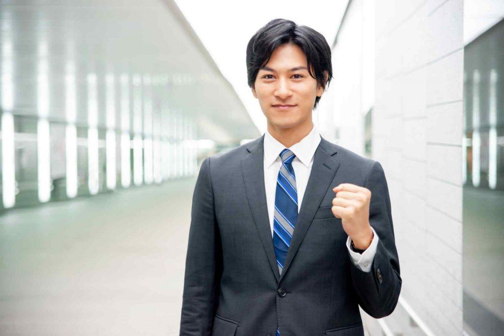 拳を握って微笑むスーツ姿の男性