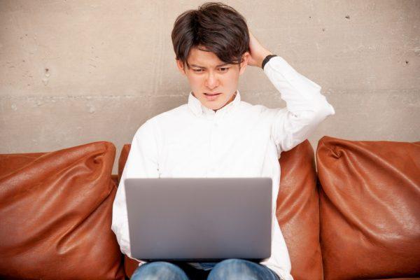 頭を搔きながらパソコンに向かう男性