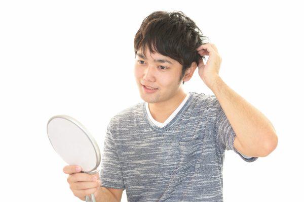 髪を触りながら鏡を見る男性
