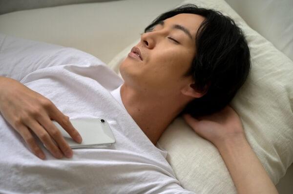 スマートフォンを持ちながら眠る男性