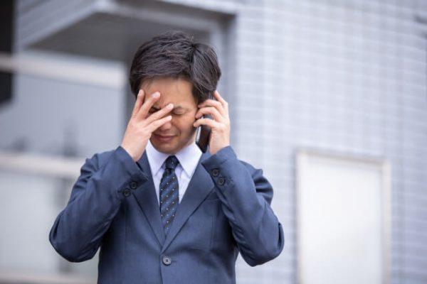 電話しながら頭を抱える男性