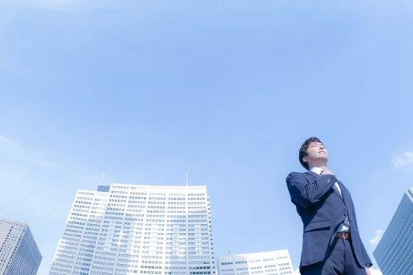 ビル背景に空を見上げるスーツの男性