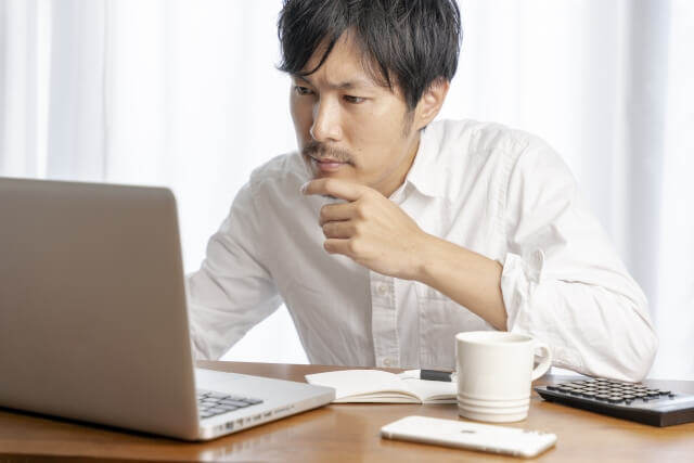 パソコンを見ながら顎に手を当てて考える男性