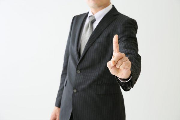 人差し指を立てて突き出すサラリーマン
